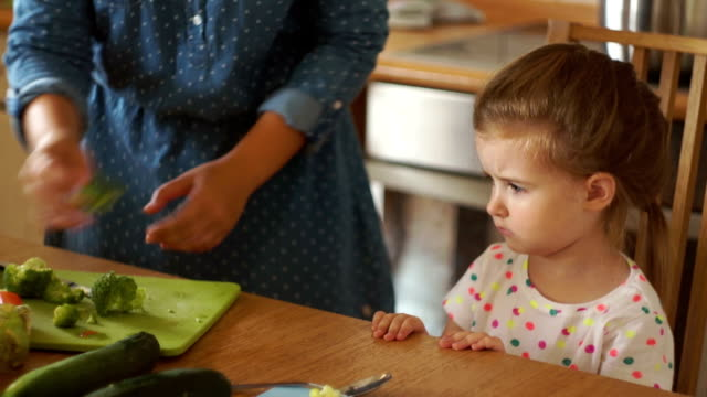 little girl in the kitchen with her mother. mom gives the daughter of broccoli. the girl resolutely repels the vegetables with her hand. the baby is very angry and does not want to eat. - broccolo video stock e b–roll