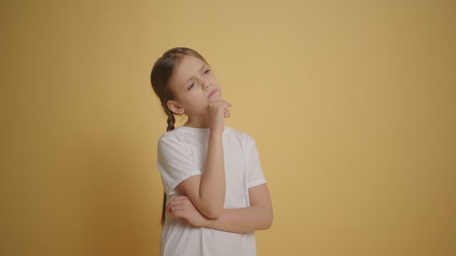 Little girl in white t-shirt thinking of an idea yellow background slow motion Little girl in white t-shirt thinking of an idea yellow background slow motion pigtails stock videos & royalty-free footage