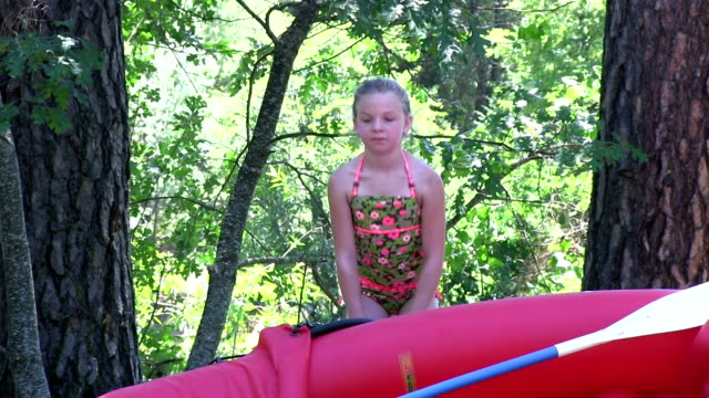 Little girl inflates kayak with river in background video