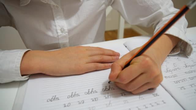 Little girl is doing homework at home. - video