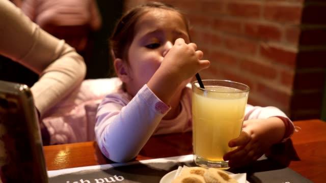little girl is drinking lemonade in a restaurant - лимонный сок стоковые видео и кадры b-roll