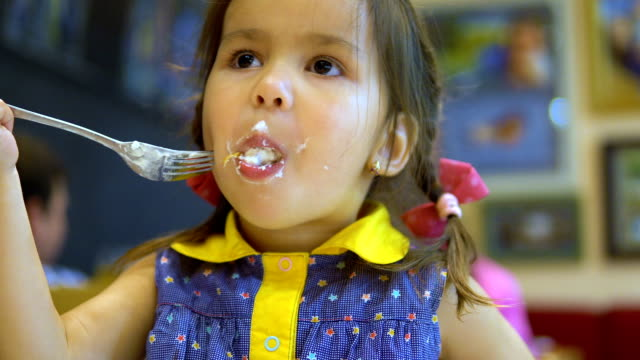 little girl is eating a cake. - desserts stock videos and b-roll footage