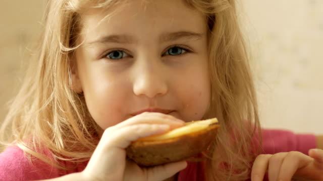 en liten flicka äter en smörgås med ost. barnet äter bröd och ost. - cheese sandwich bildbanksvideor och videomaterial från bakom kulisserna