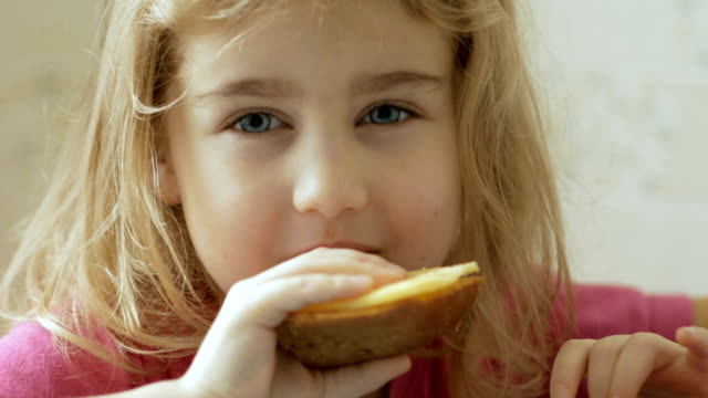 A little girl is eating a sandwich with cheese. The child eats bread and cheese. A little girl is eating a sandwich with cheese. The child eats bread and cheese. cheese stock videos & royalty-free footage
