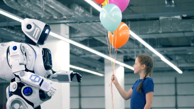 Little girl is giving balloons to a human-like cybord Little girl is giving balloons to a human-like cybord. 4K robot stock videos & royalty-free footage
