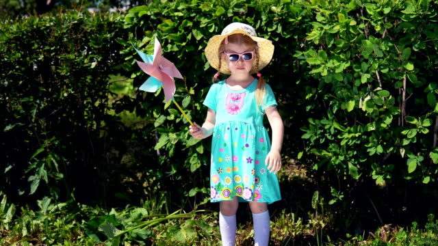 little girl is holding pinwheel on background of green bushes in summer