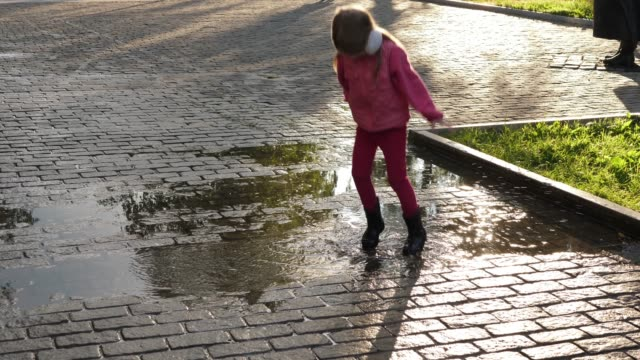 Little girl is jumping in puddle on paving stones after rain on sunny. video