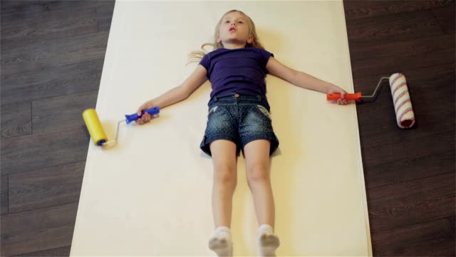 Little girl is lying on the floor on a piece of wallpaper with rollers in her hands. video