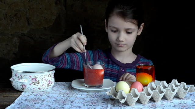Little girl is painting eggs for Easter video