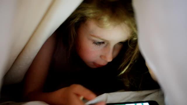 little girl is playing game on the phone under the covers. - på tå bildbanksvideor och videomaterial från bakom kulisserna