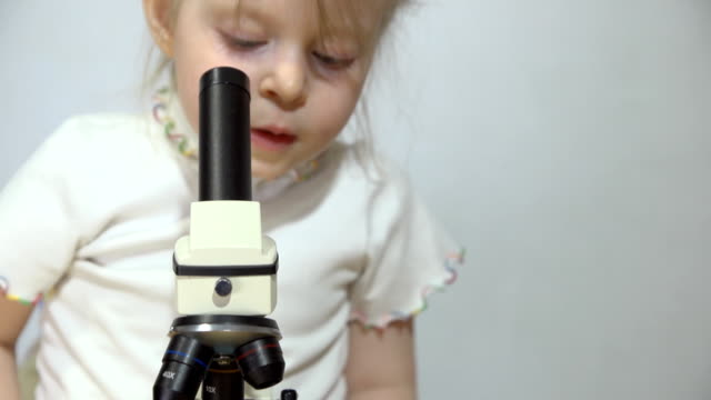 A little girl is playing with a microscope next to a white wall. video