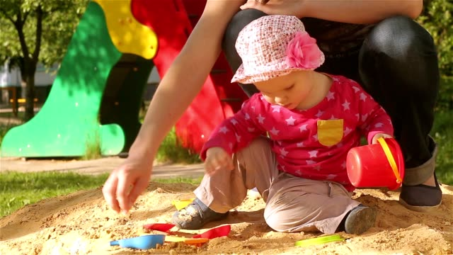 A little girl is playing with her mother in the sandbox. video