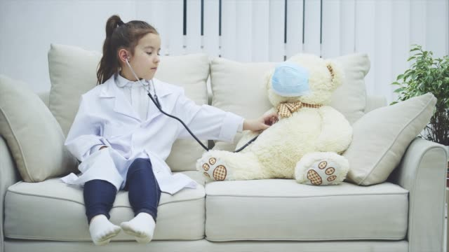 Little girl is playing with her teddy. She is a doctor. Bear is a patient. Girl is examining her teddy with stethoscope. Medicine concept. Child with a bear. Slow motion 4k video. mask disguise stock videos & royalty-free footage