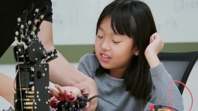 Little Girl is playing with robotic arm in a school. She is controlling it by her hand.