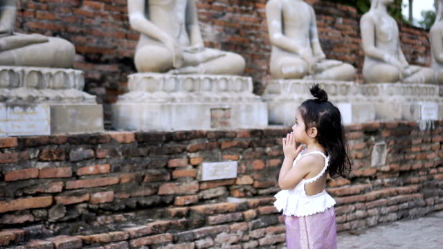 Little girl is praying Buddha Statue in temple