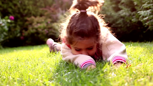 little girl is rolling in the grass video
