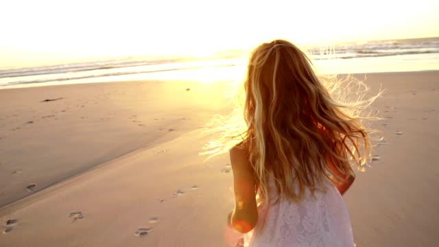 Little girl is running towards sunset video