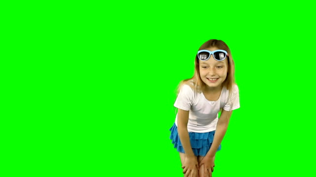Little girl is showing her finger and dancing.. Girl in sunglasses and a T-shirt. Clip contains solid green instead alpha channel. video