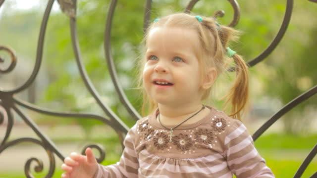 vidéos et rushes de petite fille est assise sur un banc - bivalve