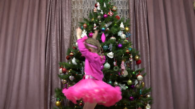 kleines mädchen dreht sich auf dem hintergrund des weihnachtsbaumes. weihnachtsbaum mit weihnachtsspielzeug und lichtern geschmückt. - kieferngewächse stock-videos und b-roll-filmmaterial
