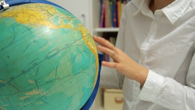 Little girl is studying the globe at home. video