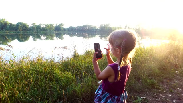Little girl is working on the smartphone. Her fingers touch the touch screen. A girl stands on the shore of the lake. Sunrise on the lake. Little girl is working on the smartphone. Her fingers touch the touch screen. A girl stands on the shore of the lake. Sunrise on the lake. Sunny summer morning. pigtails stock videos & royalty-free footage