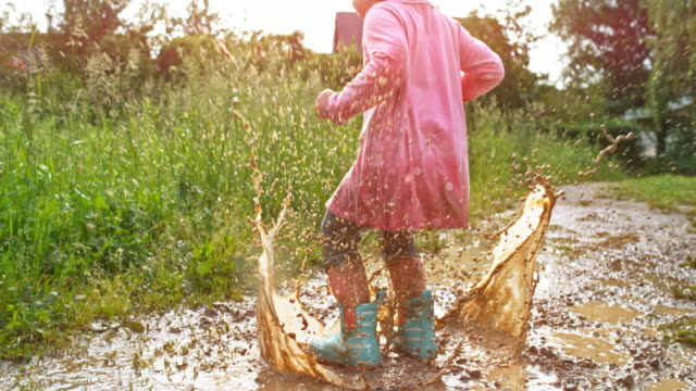 slo mo little girl jumping in a muddy puddle - children video stock e b–roll