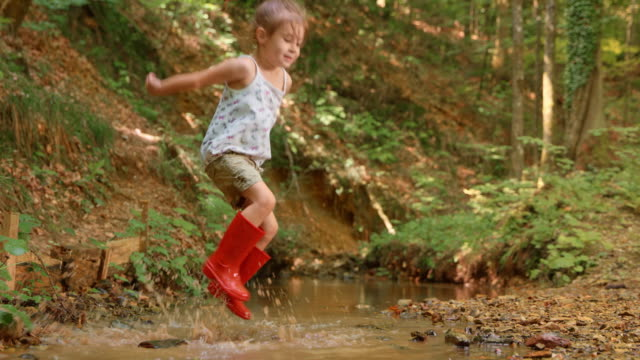 slo mo little girl jumping in a small creek in the forest wearing red rain boots - grandangolo tecnica fotografica video stock e b–roll