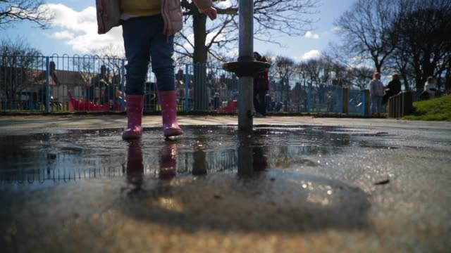vídeos de stock e filmes b-roll de little girl jumping in puddle - poça