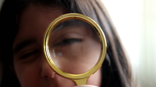 Little girl kid looking through magnifying glass