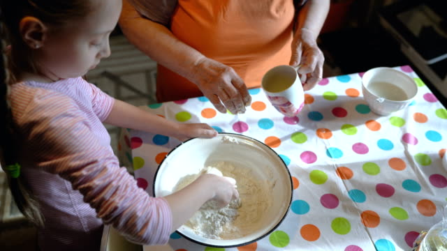 Little girl kneading dough Lovely girl with her grandmother kneading bread dough kitchen utensil stock videos & royalty-free footage