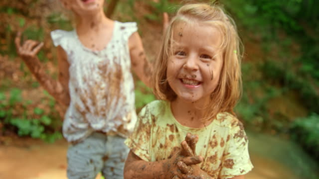 SLO MO Little girl laughing and enjoying playing with her friends in a forest creek while covered in mud Slow motion medium handheld shot of a little girl laughing while playing with her friends in a forest creek, covered in mud from head to toe. Shot in Slovenia. mud stock videos & royalty-free footage