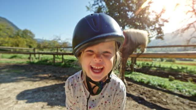 笑って乗馬乗馬ヘルメットを身に着けていると、太陽の下で外に立って少女 - 4歳から5歳点の映像素材/bロール
