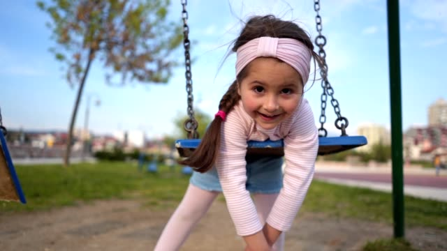 little girl laying on her belly swinging on a swing - аксессуар для волос стоковые видео и кадры b-roll