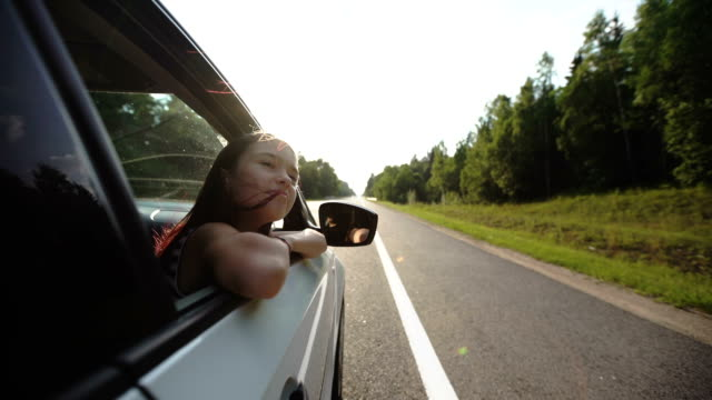 Little girl leaning out of car window video