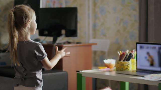 kleines mädchen lernt aus der ferne, während die schule geschlossen ist - abgeschiedenheit stock-videos und b-roll-filmmaterial