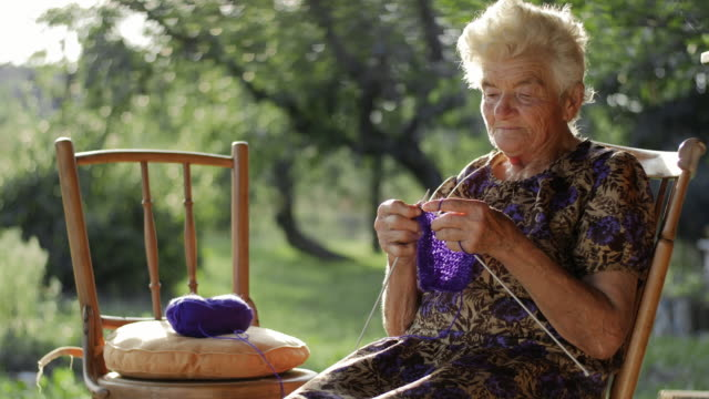 A little girl learning to knit from her grandmother video