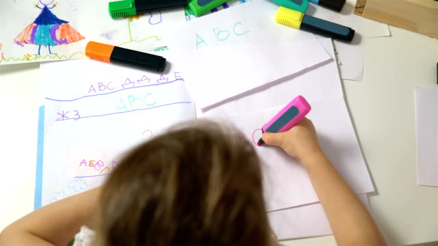 Little girl learning to write the alphabet. Dolly shot video