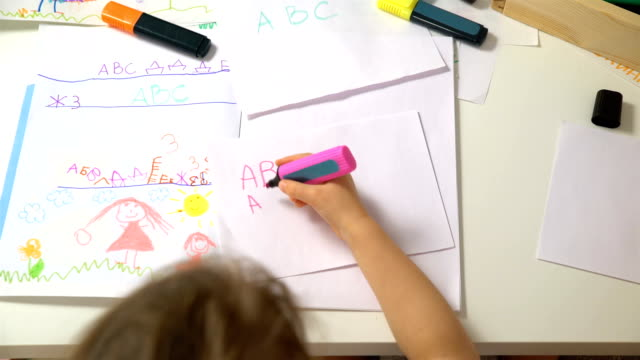Little girl learning to write the alphabet. Dolly shot ビデオ