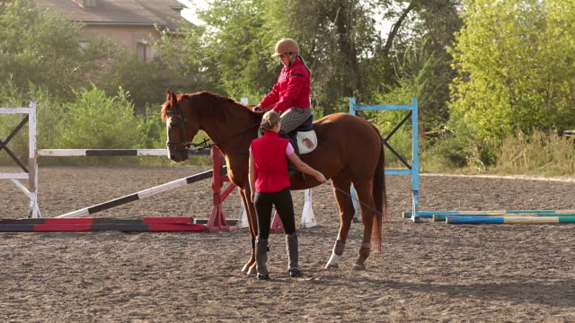 little girl learns riding with a trainer at ranch. - briglia video stock e b–roll