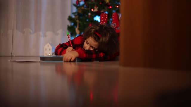 vídeos de stock, filmes e b-roll de uma garotinha deita no chão, sonha e escreve uma carta para o papai noel, ao fundo uma árvore festiva - correio correspondência