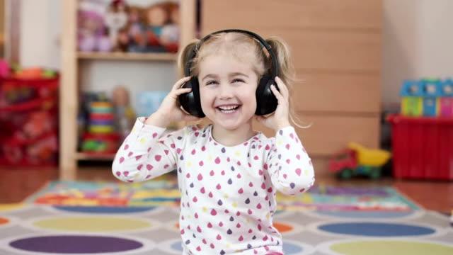 vídeos de stock, filmes e b-roll de menina ouvindo música em fones de ouvido. casa, tecnologia e música - música acústica