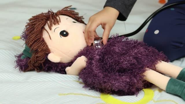 vídeos de stock, filmes e b-roll de a garotinha escuta o coração da boneca com um estetoscópio - gênero humano