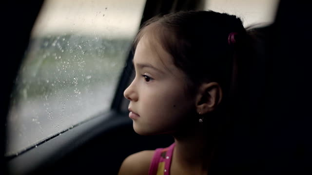 Little girl looking out from car window