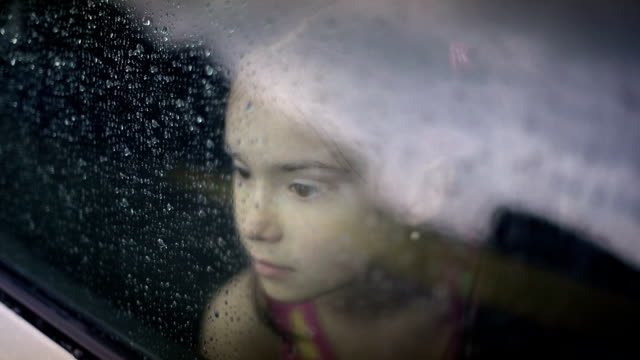 Little girl looking out from car window video