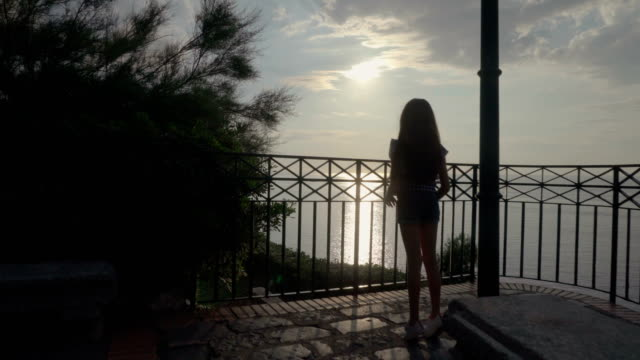 little girl looks at the the sunset on the sea, italy,lookout, calabria , summer,tropea - video di tropea video stock e b–roll