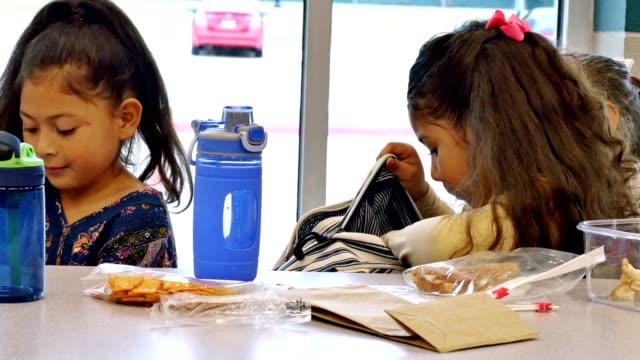 vídeos de stock e filmes b-roll de little girl looks in backpack during lunch - mochila saco