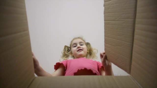 小さな女の子はボックスに見えるは、驚きと驚きを受け取るために幸せ。子供はギフトと箱を開けます。スローモーション - 荷物をとく点の映像素材/bロール