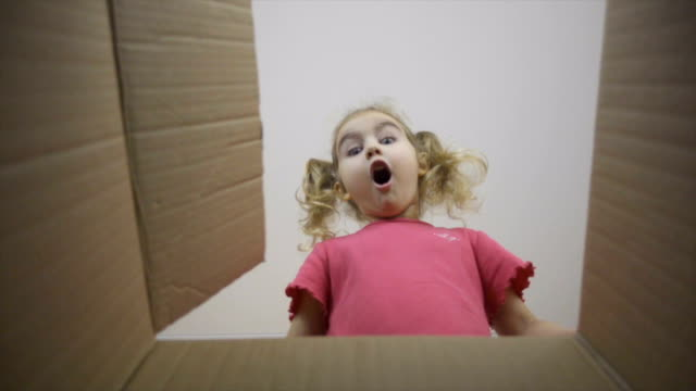 a little girl looks in the box, is surprised and happy to receive a surprise. the child opened a box with a gift.slow motion - sorpresa video stock e b–roll