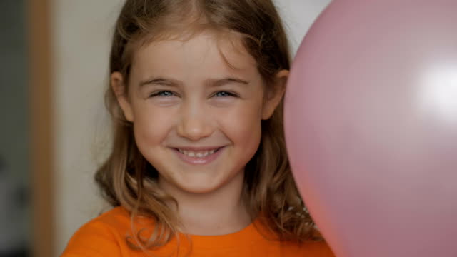 Little girl looks out from behind balloon and laughs happily. Close up portrait of a happy little child bursting in laugh. Child girl blonde with blue eyes and laughs indoors. Closeup. Slow Motion.